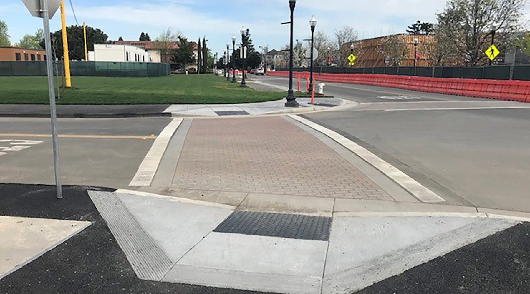 Handicap ramps with AC sidewalk complete at Murphy/McKinley intersection with new paver crosswalk.