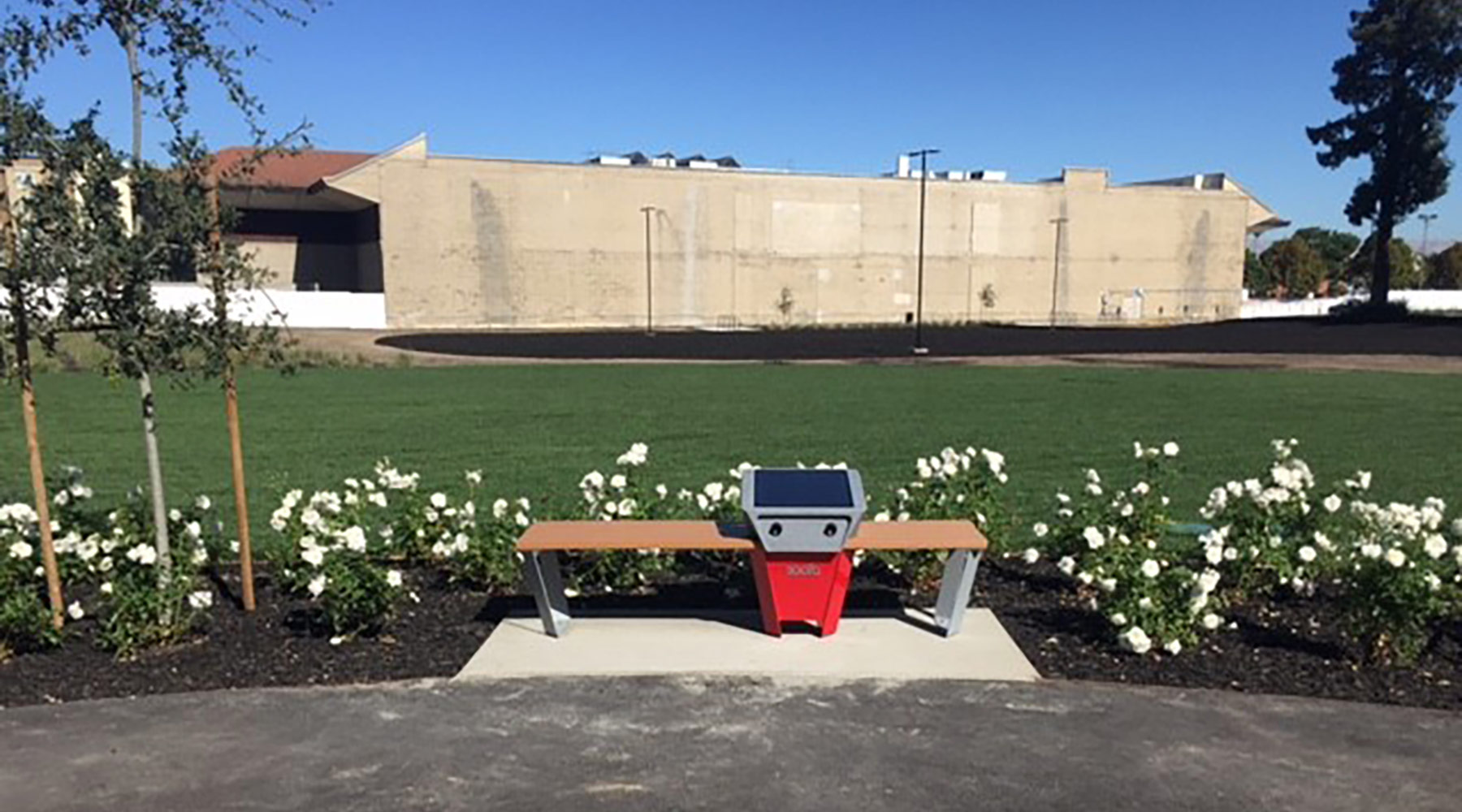Soofa solar panel bench installed on concrete pad; surrounding landscaping complete.